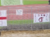 Auf dem Schild: Achtung - 2 meter Abstand zum Zaun halten - weicher Sand...
