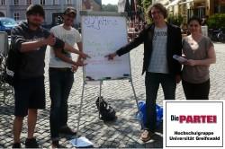 Hannes Nehls (Die PARTEI Hochschulgruppe), Christopher Riemann, Erik von Malottki und Emilia Bokov (alle Jusos) bei der Aktion auf dem Fischmarkt am Donnerstag.